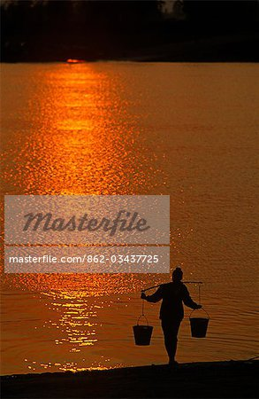 Vietnam,Hai Hung Province. Drawing water from the Red River at sunset,Hai Hung Province,Vietnam Stock Photo - Rights-Managed, Image code: 862-03437725