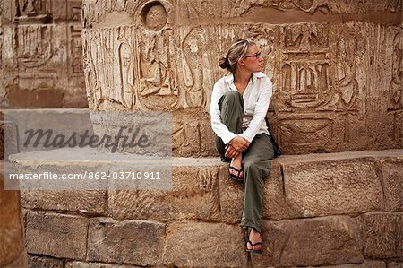 Egypt, Karnak. A tourist sits at the base of a massive stone column in the Great Hypostyle Hall. Stock Photo - Rights-Managed, Image code: 862-03710911
