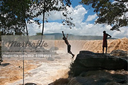 Kenya, A young man plunges into the foaming red waters of Fourteen Falls on the Athi River. Stock Photo - Rights-Managed, Image code: 862-03731461