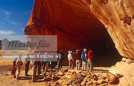 Libya, Fezzan, Jebel Akakus. Tourists gather at the mouth of Uan Amil, one of Wadi Teshuinat's caves. Stock Photo - Rights-Managed, Image code: 862-03731756