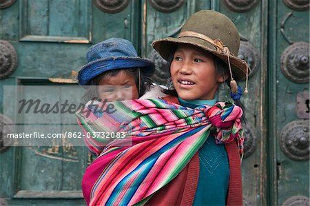 Peru, A young Peruvian girl carries her baby sister on her back beside the massive church doors of Iglesia de la Compania de Jesus in Cusco s Plaza de Armas. Stock Photo - Rights-Managed, Image code: 862-03732083