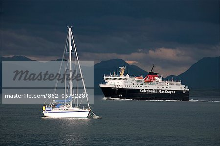 Scotland, Isle of Mull. A ferry passing a moored yacht in the Sound of Mull enroute to Tobermory on the Isle of Mull. Stock Photo - Rights-Managed, Image code: 862-03732287