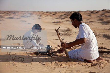 Oman, Wahiba Sands. A Bedouin guide and his son make a fire to make a coffee. Stock Photo - Rights-Managed, Image code: 862-03808149