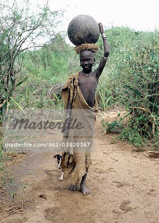 A Mursi girl, accompanied by her dog, carries a large clay pot to collect water from the Omo River. Her earlobes are already pierced and extended, and decorated with round clay discs.She is dressed in skins, attractively decorated with thin stripes.The culture, social organisation, customs and values of the people have changed little. Stock Photo - Rights-Managed, Image code: 862-03820367