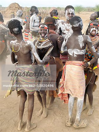 Karo men and girls enjoy a dance.The Karo excel in body art. Before dances and ceremonial occasions, they decorate themselves elaborately using local white chalk, pulverised rock and other natural pigments.The Karo are a small tribe living in three main villages along the lower reaches of the Omo River in southwest Ethiopia. Stock Photo - Rights-Managed, Image code: 862-03820496