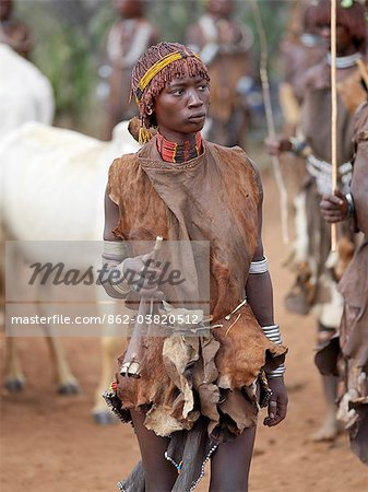 A Hamar woman holds a tin trumpet at a Jumping of the Bull ceremony.The Hamar are semi nomadic pastoralists of Southwest Ethiopia whose women wear striking traditional dress and style their red ochred hair mop fashion.The Jumping of the Bull ceremony is a rite of passage for young men. Stock Photo - Rights-Managed, Image code: 862-03820512