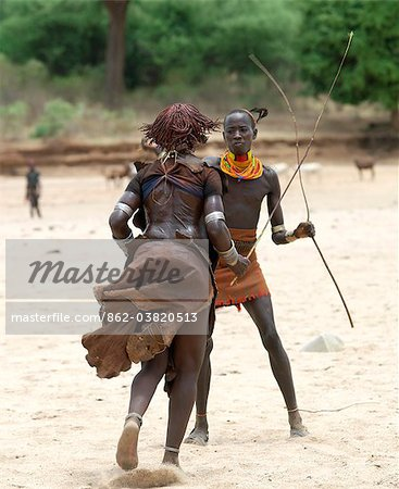 A Hamar woman being whipped by a man at a Jumping of the Bull ceremony.The semi nomadic Hamar of Southwest Ethiopia embrace an age grade system that includes several rites of passage for young men. Stock Photo - Rights-Managed, Image code: 862-03820513