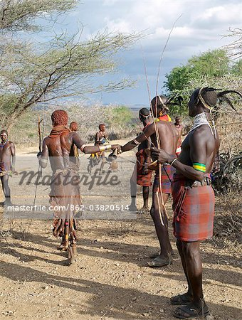 A Hamar woman implores a man to whip her at a Jumping of the Bull ceremony.Female friends and relatives of the initiate are willing whipped with pliable sticks to show their solidarity and love for him. They do not flinch or show any sign of pain.The semi nomadic Hamar of Southwest Ethiopia embrace an age grade system that includes several rites of passage for young men. Stock Photo - Rights-Managed, Image code: 862-03820514