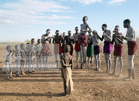 In the late afternoon, Nyangatom villagers enjoy singing and dancing. As groups of men take centre stage to jump high in the air, women and girls sing, clap to a rhythm, and move slowly towards the men. Children enjoy the excitement in the background.The Nyangatom are one of the largest tribes and arguably the most warlike people living along the Omo River in Southwest Ethiopia. Stock Photo - Rights-Managed, Image code: 862-03820538