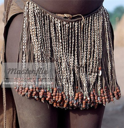 The decorated leather apron or skirt of a young Nyangatom girl. The numerous white discs woven into the strands of braided leather are made of ostrich shell.The Nyangatom are one of the largest tribes and arguably the most warlike people living along the Omo River in Southwest Ethiopia. Stock Photo - Rights-Managed, Image code: 862-03820547