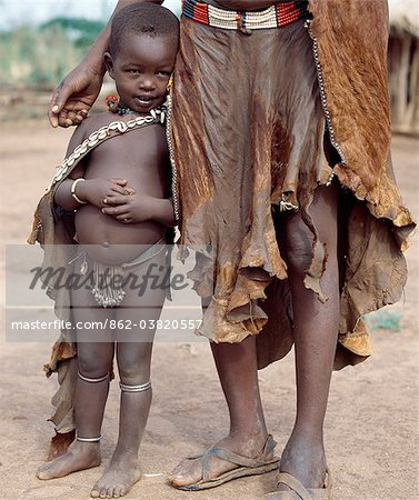 A Nyangatom mother and young daughter in typical dress. Rugged skin clothing is still widely used.The Nyangatom are one of the largest tribes and arguably the most warlike people living along the Omo River in Southwest Ethiopia. Stock Photo - Rights-Managed, Image code: 862-03820557