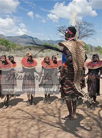 A Pokot warrior wearing a cheetah skin jumps high in the air surrounded by  young women to celebrate an Atelo ceremony. The Pokot are pastoralists speaking a Southern Nilotic language. Stock Photo - Rights-Managed, Image code: 862-03888696