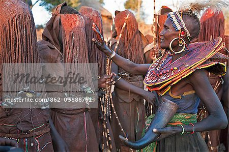 At the start of a Ngetunogh ceremony, the mothers of Pokot initiates will smear animal fat on the boys masks as a blessing. The boys must wear goatskins, conceal their faces with masks made from wild sisal (sansevieria) and carry bows with blunt arrows until this ceremony is over. Stock Photo - Rights-Managed, Image code: 862-03888761