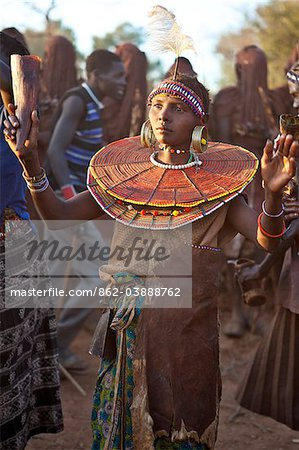 During a Ngetunogh ceremony, the mother of a Pokot initiate sings and dances holding high the cowhorn container she used to smear fat over the masks of her son and other boys as a blessing. Stock Photo - Rights-Managed, Image code: 862-03888762