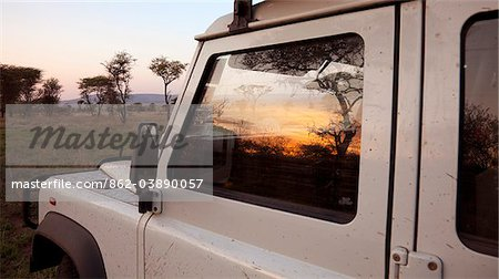 Tanzania, Serengeti. Sunrise over the bush is reflected in the window of a Land Rover. Stock Photo - Rights-Managed, Image code: 862-03890057