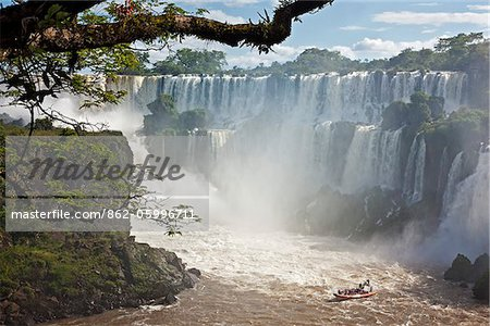 An inflatable boat takes visitors into white water at the bottom of one of the spectacular Iguazu Falls of the Iguazu National Park, a World Heritage Site. Argentina Stock Photo - Rights-Managed, Image code: 862-05996711