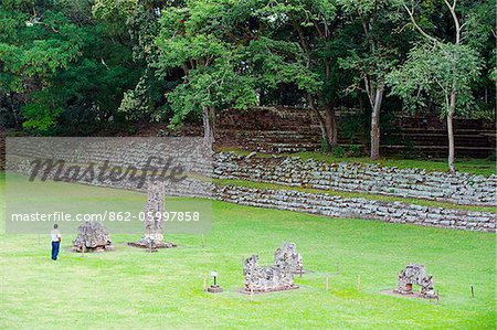 Central America, Honduras, Copan Ruins, Mayan archeological site, Copan Ruins, Unesco World Heritage site; tourist looking at ruined statues Stock Photo - Rights-Managed, Image code: 862-05997858