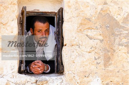 Yemen, Sana'a Province, Haraz Mountains, Al Hajjarah. A man looks out from a window. Stock Photo - Rights-Managed, Image code: 862-05999734