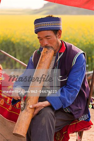 China, Yunnan, Luoping. A man of the Buyi ethnic minority group enjoying a smoke with a large water pipe amongst the mustard fields of Luoping. Stock Photo - Rights-Managed, Image code: 862-06676223