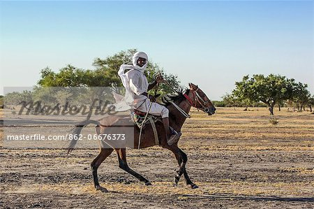 Chad, Kanem, Bahr el Ghazal, Sahel. A Kanembu horseman gallops home. Stock Photo - Rights-Managed, Image code: 862-06676373
