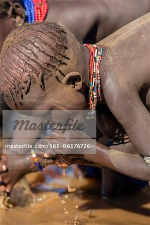 A young Dassanech girl drinking dirty water from the Omo River, Ethiopia Stock Photo - Rights-Managed, Image code: 862-06676726