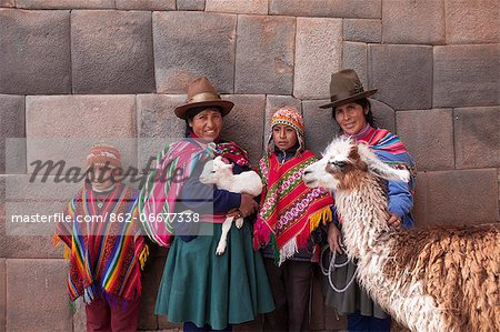 South America, Peru, Cusco. Quechua people standing in front of an Inca wall, holding a lamb and a llama and wearing traditional clothing including a bowler hat, liclla, chullo and poncho    while talking on a cell phone in the UNESCO World Heritage listed former Inca capital of Cusc Stock Photo - Rights-Managed, Image code: 862-06677338