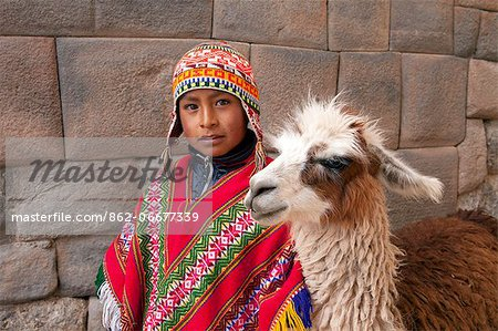 South America, Peru, Cusco. A Quechua boy in a poncho and a chullo woollen cap with a Llama standing in front of an Inca wall in the UNESCO World Heritage listed former Inca capital of Cusco Stock Photo - Rights-Managed, Image code: 862-06677339