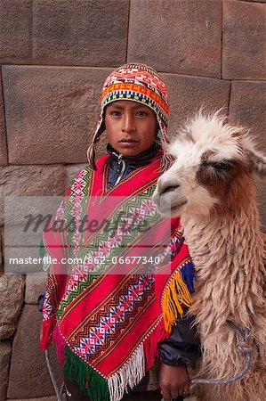 South America, Peru, Cusco. A Quechua boy in a poncho and a chullo woollen cap with a Llama standing in front of an Inca wall in the UNESCO World Heritage listed former Inca capital of Cusco Stock Photo - Rights-Managed, Image code: 862-06677340
