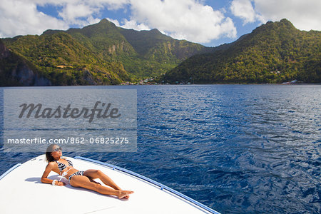 Dominica, Soufriere. A young woman sunbathes on the foredeck of a Powerboat near Soufriere. (MR). Stock Photo - Rights-Managed, Image code: 862-06825275