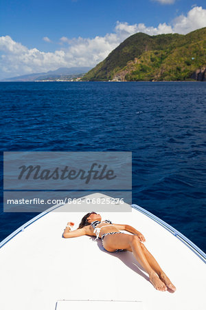 Dominica, Soufriere. A young woman sunbathes on the foredeck of a Powerboat near Soufriere. (MR). Stock Photo - Rights-Managed, Image code: 862-06825276