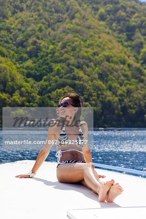 Dominica, Soufriere. A young woman sunbathes on the foredeck of a Powerboat near Soufriere. (MR). Stock Photo - Rights-Managed, Image code: 862-06825277