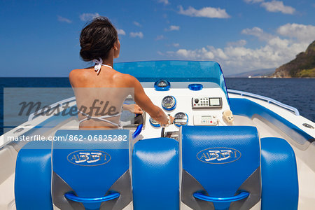 Dominica, Soufriere. A young woman at the helm of a  Powerboat near Soufriere. (MR). Stock Photo - Rights-Managed, Image code: 862-06825282