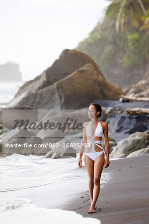 Dominica, Riviere Cyrique. A young woman walks along the black sand beach at Wavine Cyrique. (MR). Stock Photo - Rights-Managed, Image code: 862-06825293