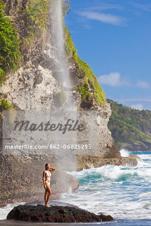 Dominica, Riviere Cyrique. A young woman stands under the waterfall at Wavine Cyrique. (MR). Stock Photo - Rights-Managed, Image code: 862-06825295
