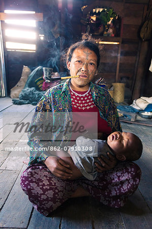 Myanmar, Chin State, Kempetlet. Chin woman with  traditional facial tattoo, holding her baby boy and smoking pipe. (MR) (PR) Stock Photo - Rights-Managed, Image code: 862-07910308