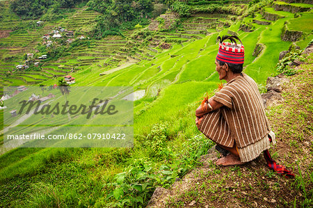 Asia, South East Asia, Philippines, Cordilleras, Banaue; an Ifugao man in traditional clothing looks out over the UNESCO World heritage listed Ifugao rice terraces between in Batad Stock Photo - Rights-Managed, Image code: 862-07910422