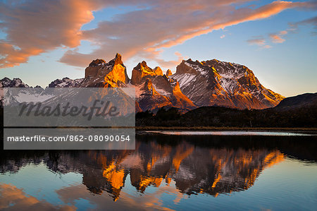 Chile, Torres del Paine, Magallanes Province. Sunrise over Torres del Paine reflected in the waters of Lake Pehoe in the foreground. One of the principal attractions of the National Park is the magnificent Paine massif. Stock Photo - Rights-Managed, Image code: 862-08090054