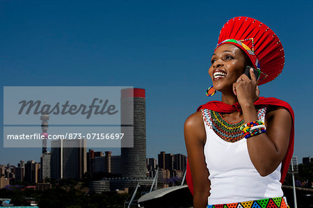 Traditionally dressed African woman talks on cellphone with cityscape in background Stock Photo - Rights-Managed, Image code: 873-07156697