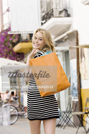 Youn woman in street holding bags Stock Photo - Rights-Managed, Image code: 877-06832532