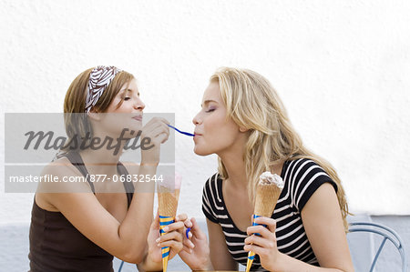 Two young women eating ice cream Stock Photo - Rights-Managed, Image code: 877-06832544