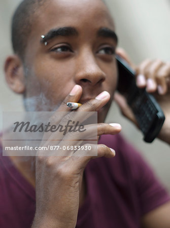 Teenage boy smoking while phoning Stock Photo - Rights-Managed, Image code: 877-06833930