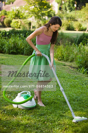 Young woman vacuuming grass Stock Photo - Rights-Managed, Image code: 877-06834303