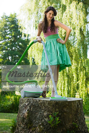 Young woman vacuuming on tree stump Stock Photo - Rights-Managed, Image code: 877-06834306
