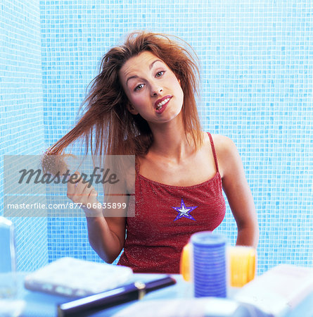 Portrait woman untangling her hair in bathroom Stock Photo - Rights-Managed, Image code: 877-06835899