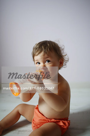 A 15 months old baby girl posing with her baby bottle Stock Photo - Rights-Managed, Image code: 877-08031247