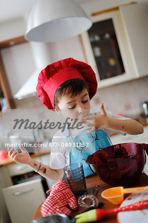 A little boy tasted the chocolate cake preparation Stock Photo - Rights-Managed, Image code: 877-08031252