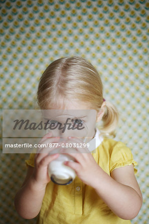 A 2 years old girl posing as she 's drinking a glass of milk Stock Photo - Rights-Managed, Image code: 877-08031299