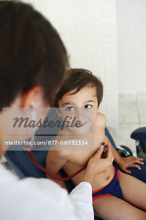Doctor examining young patient, using stethoscope Stock Photo - Rights-Managed, Image code: 877-08031334