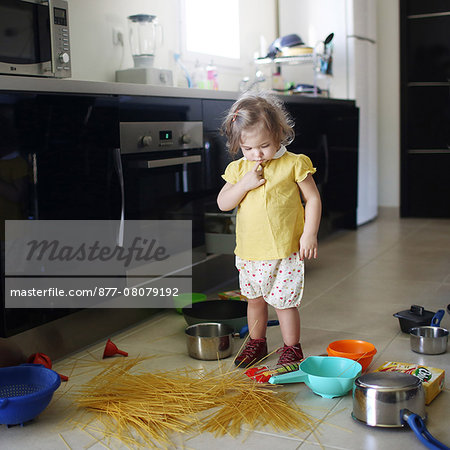 A 2 years old little girl posing in a kitchen in which she made the mess Stock Photo - Rights-Managed, Image code: 877-08079192