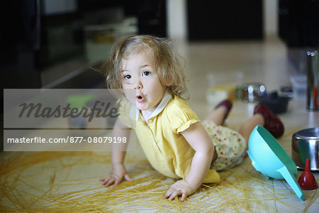 A 2 years old little girl posing in a kitchen in which she made the mess Stock Photo - Rights-Managed, Image code: 877-08079198